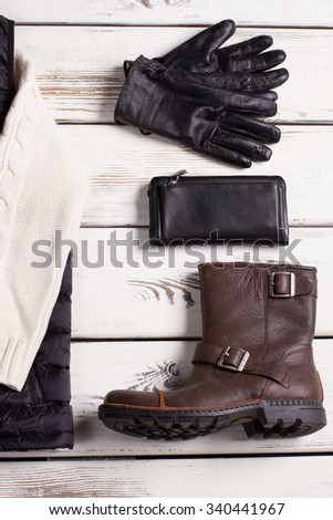 Leather men's accessories and shoes on a white wooden background.