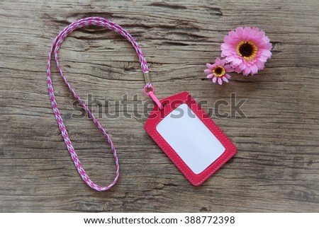Leather name tag with neck strap on wooden background - stock photo