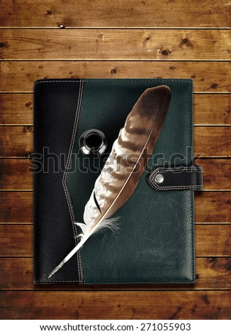Leather notebook and feather with ink bottle on a wooden board.