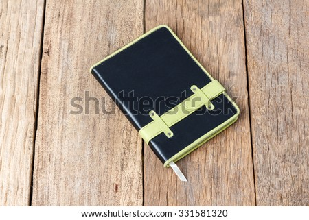Leather notebooks on wooden background - stock photo