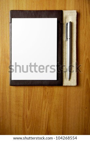 Leather notepad with paper and pen on wood desk - stock photo