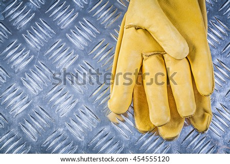 Leather protective gloves on corrugated metal plate construction concept.