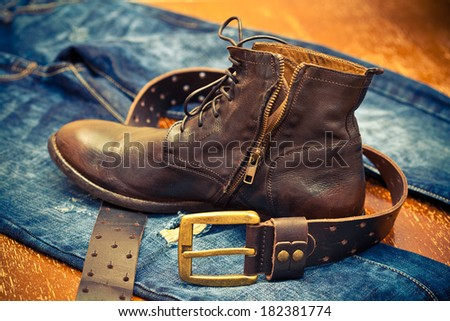 leather shoes, leather belt with a gold buckle, jeans. Cowboy style. Vintage style - stock photo