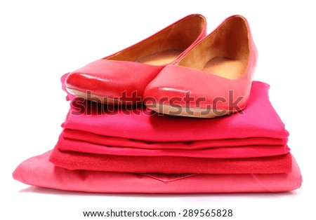 Leather shoes of woman and pile of red shirts and clothes, concept of fashion and red color. Isolated on white background