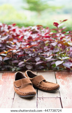 Leather shoes on the old wooden floor.Brown shoe on brown wood in the garden home.Vintage brown shoe. - stock photo