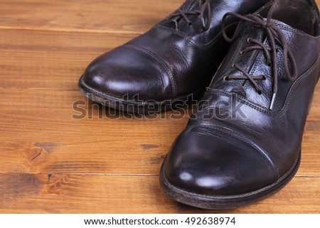 Leather shoes winter care. Stylish male boots on wooden background