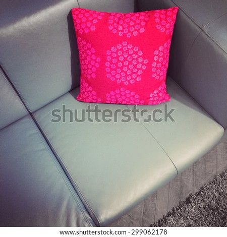 Leather sofa with bright red cushion. Modern furniture. - stock photo