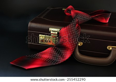 Leather suitcase with red silk tie. - stock photo