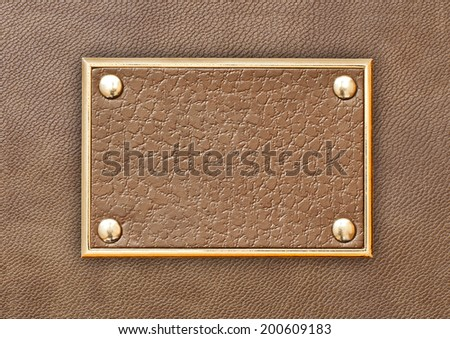 Leather tag in a metal frame on a background of brown leather