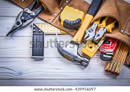 Leather tool belt with construction tooling on wooden board maintenance concept.