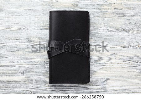 Leather wallet on white wooden background - stock photo