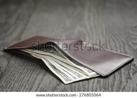 leather wallet on wood table with dollar bills - stock photo