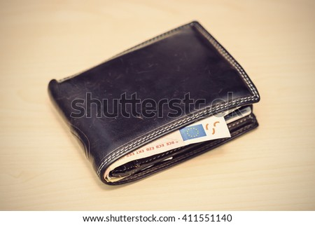 leather wallet with 50 Euro banknote inside on wooden table, vintage filtered style  - stock photo