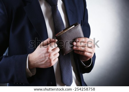 Leather wallet with money in male hands on dark background - stock photo