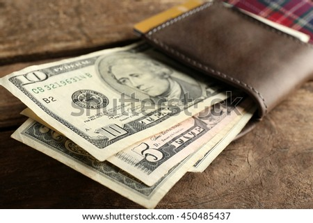 Leather wallet with money on wooden table