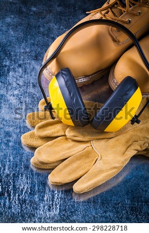 Leather working boots protective gloves and noise reduction headphones on scratched metallic surface construction concept. - stock photo