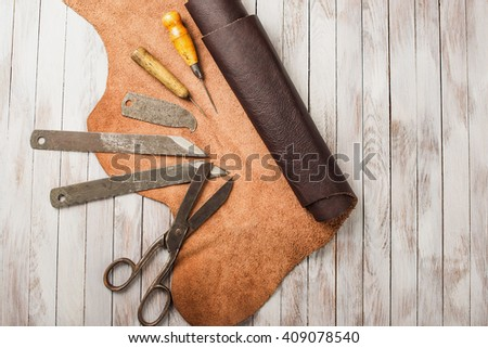 Leathersmith's work desk . Pieces of hide and leather working tools on a work table.