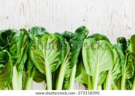 Leaves and stalks of tatsoi on a wooden surface - stock photo