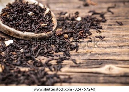 Leaves of black tea in wooden spoon - stock photo