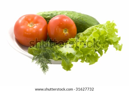 Leaves of green salad with red tomato, cucumber isolated - stock photo