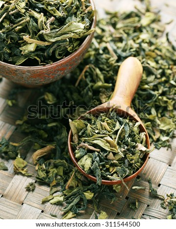 leaves of green tea with wooden Spoon. - stock photo