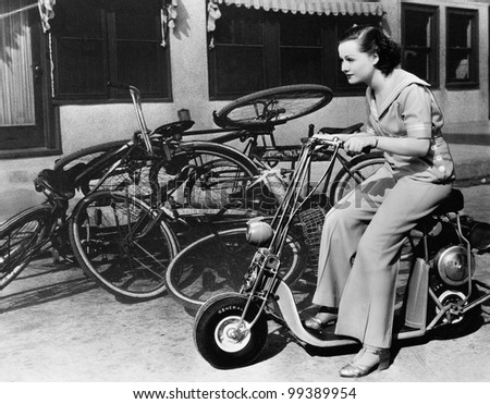 Leaving bicycles in the dust, a young woman fancies a miniature motorbike - stock photo