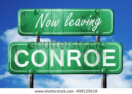 Leaving conroe, green vintage road sign with rough lettering