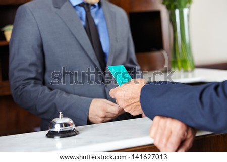 Leaving guest giving his room key card to hotel receptionist