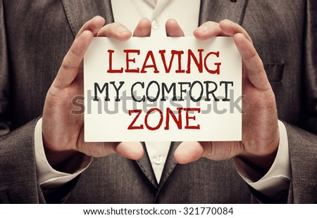 Leaving My Comfort Zone. Businessman holding a card with motivational message - stock photo