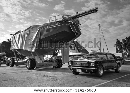 LEBA, POLAND - AUGUST 31: Black and white photo of American muscle car Ford Mustang parked next to luxury yacht in a port in Leba on August 31, 2015 - stock photo