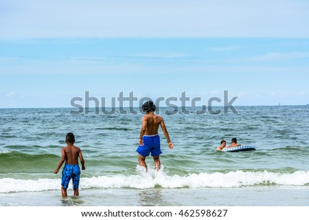 LEBA, POLAND - JULY 31, 2016: Black boys in the sea playing in water, holiday summer time over Baltic Sea in season