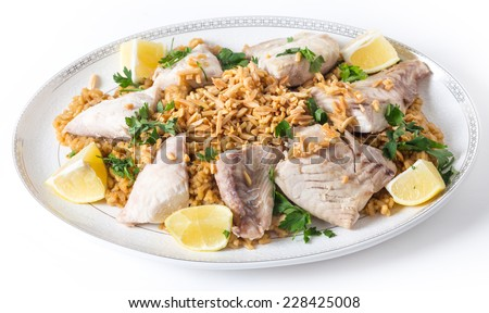 Lebanese-style fried fish on a serving dish with caramelised onion flavoured rice and roasted almond slivers. - stock photo