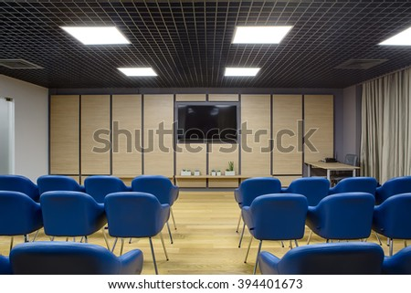 Lecture room in a coworking. There are a lot of blue chairs. Background wall is dark gray with wooden panels and TV on it. There are plants in the pots under the TV. On the left there is a white wall