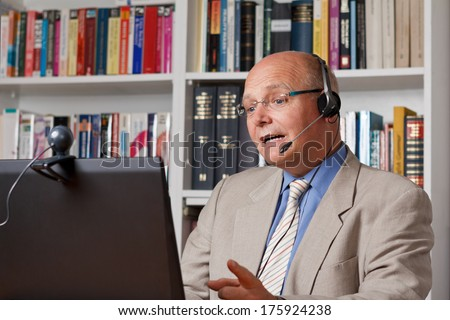 Lecturer at an online workshop with computer, camera and headset - stock photo
