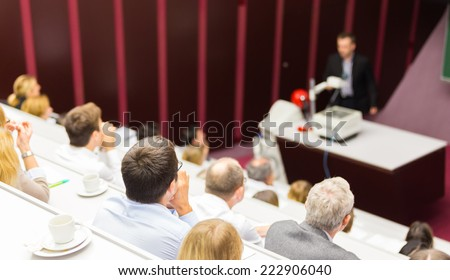 Lecturer at university. Medical expert giving a talk as an faculty professor. Participants listening to lecture and making notes. - stock photo