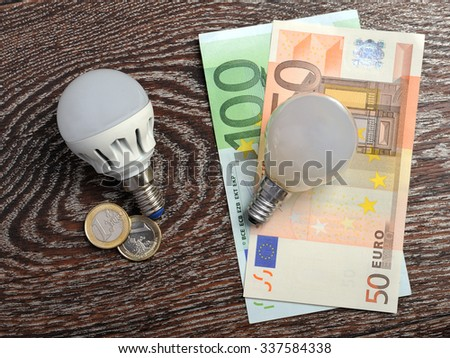 LED bulb and incandescent lamp at euro bills - stock photo