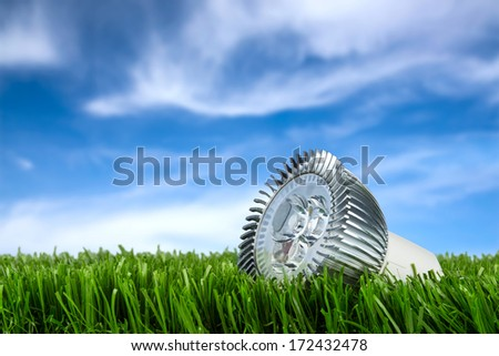 led bulb on grass in front of blue sky - stock photo