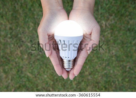 LED Bulb with lighting on hand with nature background - stock photo