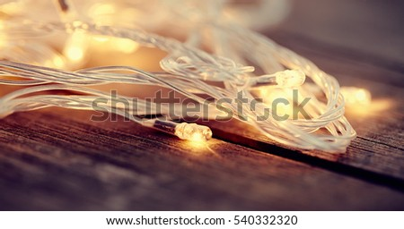 LED bulbs of a Christmas garland on a wooden background.