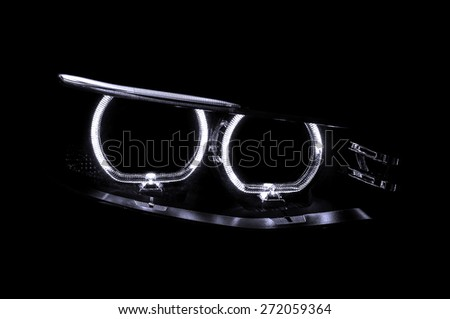 LED headlights of car on black background. Exterior detail. - stock photo