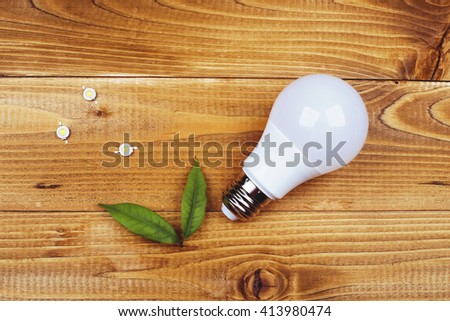 Led lamp green technologies background. Wooden table, eco lamp and green leaves. Energy efficiency concept. Led lamp with contacts and LED board on a wooden table. Job electrician. - stock photo