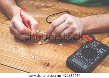 Led lamp with contacts and LED board on a wooden table. Job electrician. Male hands fixing the LEDs lamps. Workplace of electrician. Led technologies concept - stock photo