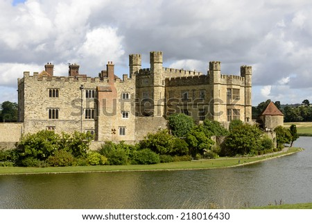 Leeds castle east side , Maidstone, England view of the eastern side of medieval castle and its moat,  shot in bright light under a cloudy sky