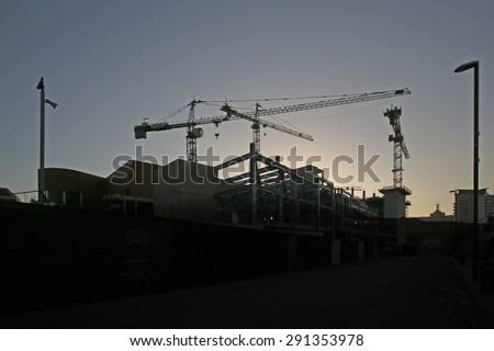 LEEDS, UK - JUNE 6, 2015: Cranes back lit against the morning sunrise. The Leeds City Region is the UK largest economy and population centre outside London, generating 4% of national economic output - stock photo