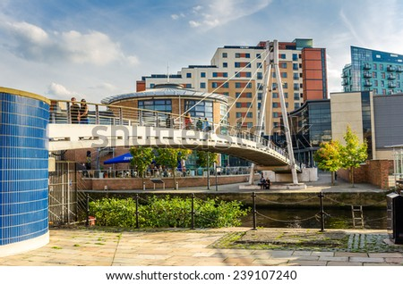 Leeds, UK - September 28, 2014: Tourists and Locals on Centenary Bridge on a warm autumn day. This footbridge, open in November 1992, allows easy access to the old Brewery Wharf venue and beyond. - stock photo