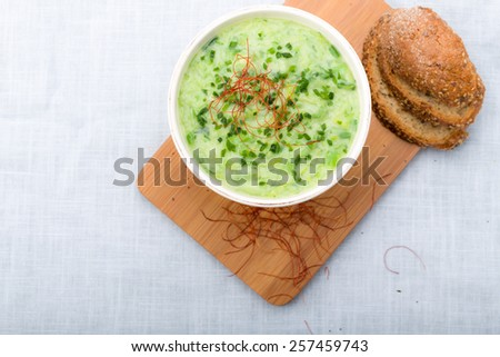Leek soup with fresh chives sprinkled, chilli and sliced bread