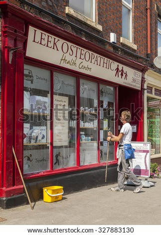 Leek, Staffordshire England. August 12th 2015: Window cleaner cleaning Leek Osteopathic health center shop window. - stock photo