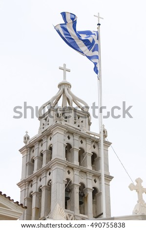 Lefkes, Paros, Greek Island church cathedral wth Greece national flag in wind