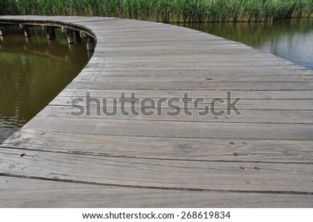 Left curve wooden bridge path in lake at wetland park - stock photo