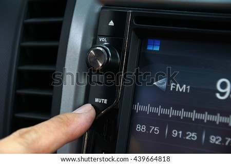 Left forefinger pressing a mute control knob of the car's audio system. - stock photo